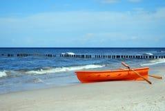 Orange Rettungsboot auf einem Strand Stockfotos