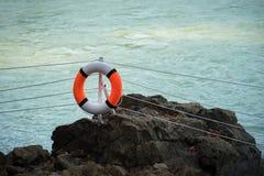 Orange Rettungsring, der an einer Spalte in einem Park nahe dem See hängt Stockfoto