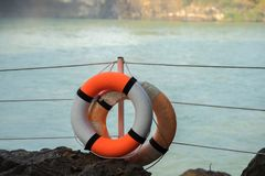 Orange Rettungsring, der an einer Spalte in einem Park nahe dem See hängt Lizenzfreies Stockbild