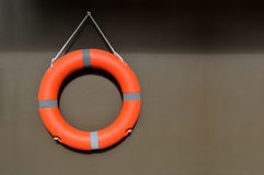 Orange Rettungsring, der an einer Wand hängt Stockfotografie