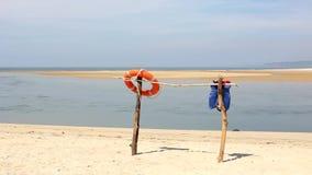 Orange Rettungsringring und blaue Schwimmweste auf einem Bambusstand auf einem sandigen Strand gegen den Hintergrund der Seebucht stock video footage