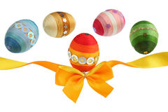 Orange ribbon and colorful eggs Stock Photography