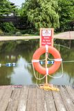 Orange ring buoy and swim at your own risk sign on post near lake royalty free stock photography
