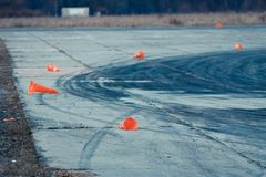 Orange road cones lying destroyed on concrete beton plates with rubber traces left by sport cars tires during drifting competiti. Destroyed orange road cones stock photography
