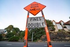 Orange road construction sign on the street stock photos