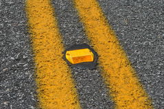 Orange  road  reflector. A  reflector  shines  at  night  to  highlight  lanes  in  a  road Stock Photos