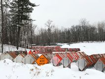 Orange ROAD WORK AHEAD sign among dozens of road signs in a snowy lot stock photos