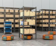 Orange robots carrying pallets with goods in modern warehouse Stock Photos