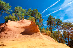 Orange rock formation and trees under blue sky on Le Sentier des Stock Photography