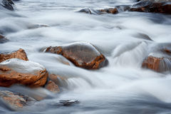 Rocks in the water. Orange rocks in the river water Stock Images