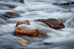 Rocks in the water. Orange rocks in the river water Royalty Free Stock Images