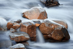Rocks in the water. Orange rocks in the river water Stock Photos