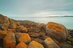 Orange Rocky Coastline Stock Images