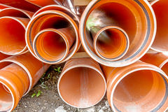 Orange Rohre PVCs, Rohre werden in einem Stapel an der Baustelle gestapelt, Lizenzfreies Stockfoto