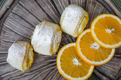 Orange rolls on a textured cutting Board. From under oranges with powdered sugar Royalty Free Stock Images