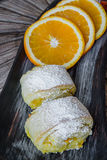 Orange rolls on a textured cutting Board. From under oranges with powdered sugar Royalty Free Stock Photos