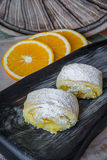 Orange rolls on a textured cutting Board. From under oranges with powdered sugar Stock Image