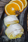 Orange rolls on a textured cutting Board. From under oranges with powdered sugar Stock Photo