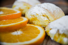 Orange rolls on a textured cutting Board. From under oranges with powdered sugar Stock Images