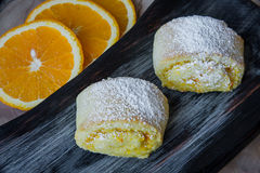 Orange rolls on a textured cutting Board. From under oranges with powdered sugar Royalty Free Stock Photo