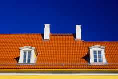 Orange roof against blue sky. Orange roof with two windows and chimneys against blue sky Royalty Free Stock Photography