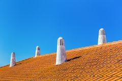 Orange roof tiles with four white chimneys Royalty Free Stock Image