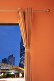 Orange room have a window with blinds you can see City at twilig Stock Images