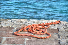 Orange rope on a rocky pier Stock Photos