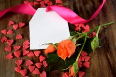An orange rose, a blank note and little hearts scattered on wooden background Royalty Free Stock Image