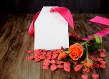 An orange rose, a blank note and little hearts scattered on wooden background Stock Photos