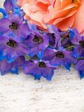 Orange rose and blue larkspur on the white painted background Royalty Free Stock Photo