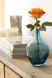 Home interior details orange and blue. Orange rose in blue vase with out of focus magazine and candles behind Royalty Free Stock Photos