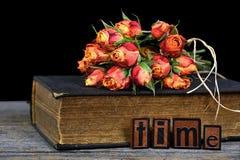 Orange rose bouquet on vintage book Stock Photo