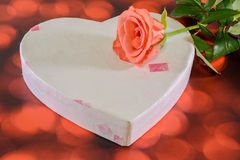 Orange rose flower with heart shape gift box, red bokeh background Stock Photos
