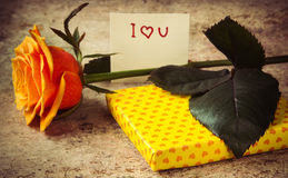 Orange rose, gift covered in hearted paper and note I love you Royalty Free Stock Photos