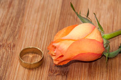 Orange rose with golden ring on the wooden board Royalty Free Stock Images