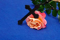 An orange rose with rosary beads. On a blue background stock images