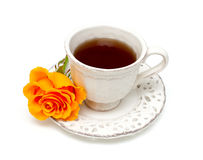 Orange rose and white cup. Orange rose and white tea cup isolated on white background stock photos