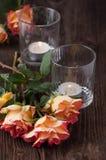 Orange Rosen mit Blitzkerze Stockfoto