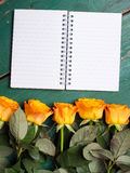 Orange roses and blank notebook  on wodden background Stock Photo