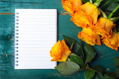 Orange roses and blank notebook  on wodden background Stock Photos