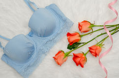 Orange roses and blue bodice with lace on white fur. Fashionable concept. Top view, close-up.  Royalty Free Stock Photo