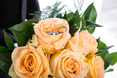 Orange roses bunch with wedding rings. Stock Photo