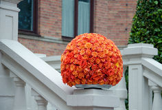 Orange roses centerpiece flower ball. Orange rose flower ball, a large outdoor festive centerpiece standing on the stairs with a white fence and brick building stock photo