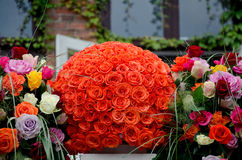 Orange roses centerpiece flower ball. Orange rose flower ball, a large outdoor festive centerpiece standing on the stairs with a white fence with colorful royalty free stock photo