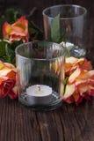 Orange roses with lightning candle Royalty Free Stock Image