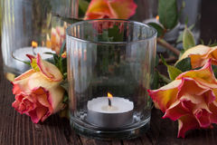 Orange roses with lightning candle Stock Photography