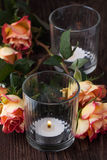 Orange roses with lightning candle Royalty Free Stock Photos