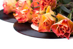 Orange roses with old records over white Royalty Free Stock Photos