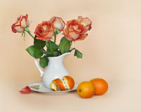 Orange roses in a white jug and oranges Royalty Free Stock Photography